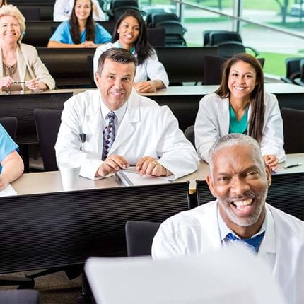 Diverse staff of doctors, nurses, and administrators in hospital are attending a healthcare conference or training seminar to review hospital policies.