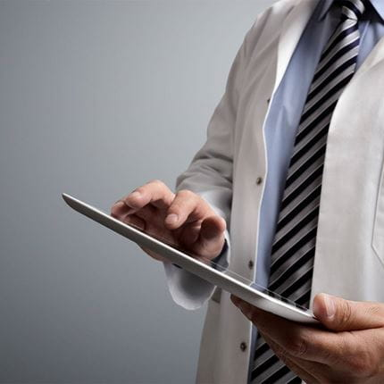A doctor uses a digital tablet.